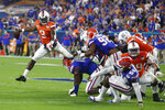Virginia quarterback Bryce Perkins (3) breaks away from the pack to throw the ball during the first half of the Orange Bowl NCAA college football game against Florida, Monday, Dec. 30, 2019, in Miami Gardens, Fla. (AP Photo/Brynn Anderson)