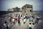 FILE - In this June 29, 2015, file photo, tourists visit a part of Hashima Island, commonly known as Gunkanjima, which means