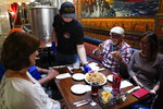 Tim Stevenson serves an appetizer to customers at San Pedro Brewing Company on Friday, May 29, 2020, in the San Pedro area of Los Angeles. (AP Photo/Ashley Landis)