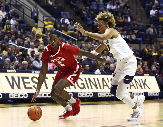 Boston University guard Walter Whyte (5) is defended by West Virginia forward Emmitt Matthews Jr. (11) during the first half of an NCAA college basketball game Friday, Nov. 22, 2019, in Morgantown, W.Va. (AP Photo/Kathleen Batten)