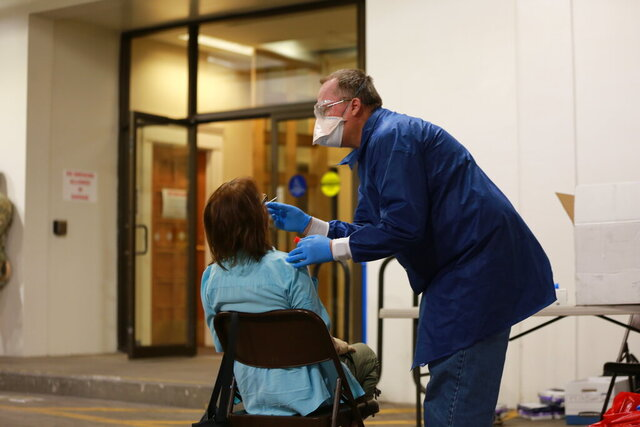 A healthcare worker administers a routine COVID-19 test to state Sen. Mimi Steward, of Bernalillo, on Monday, June 15, 2020, in Santa Fe, N.M.. Legislators and state workers were tested in a parking garage the state Capitol ahead of a special legislative session called in response to the budget crunch caused by the coronavirus pandemic. (AP Photo/Cedar Attanasio)