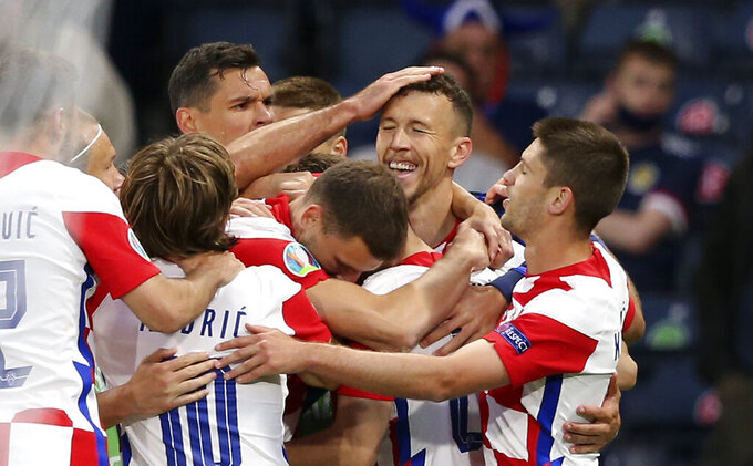 Croatia's Ivan Perisic, 2nd from right, is celebrated after scoring his side's third goal during the Euro 2020 soccer championship group D match between Croatia and Scotland at the Hampden Park Stadium in Glasgow, Tuesday, June 22, 2021.(Robert Perry/Pool via AP))