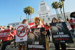 FILE - In this Sept. 18, 2018, file photo, Margo Paine, center, joins protesters with the People for the Ethical Treatment of Animals (PETA) holding signs to ban fur in Los Angeles prior to a news conference at Los Angeles City. California will be the first state to ban the sale and manufacture of new fur products and the third to bar most animals from circus performances under a pair of bills signed Saturday, Oct. 12, 2019 by Gov. Gavin Newsom. (AP Photo/Richard Vogel, File)