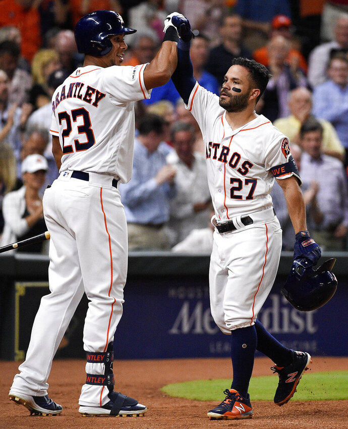 Houston Astros' Jose Altuve (27) celebrates his solo home run off New York Yankees starting pitcher Jonathan Loaisiga with Michael Brantley during the third inning of a baseball game against the New York Yankees, Tuesday, April 9, 2019, in Houston. The home run was Altuve's 100th for his career. (AP Photo/Eric Christian Smith)