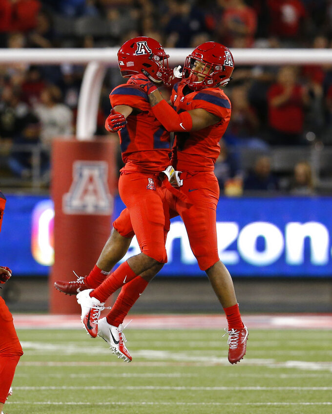 Arizona safety Scottie Young Jr., right, celebrates with Malik Hausman (23) after intercepting a pass in the first half during an NCAA college football game against Oregon, Saturday, Oct. 27, 2018, in Tucson, Ariz. (AP Photo/Rick Scuteri)
