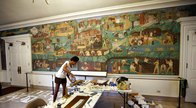 FILE - In this Aug. 15, 2018, file photo, artist Karyn Olivier creates contextual art around the University of Kentucky's controversial 1930s mural, seen on the wall in the background, in Memorial Hall in Lexington, Ky. A Kentucky writer and his wife sued the university Monday, July 6, 2020, to try to stop the removal of the mural that has been the object of protest for its depictions of Black people and Native Americans. University President Eli Capilouto announced in June 2020 that the mural would be coming down. Meanwhile, the National Coalition Against Censorship made public a letter that separately asks the university to halt its plans, saying it would negate the work of Olivier, a Black artist who created an installation that responds to the mural. (Charles Bertram/Lexington Herald-Leader via AP, File)
