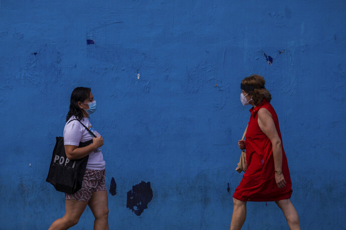 Two woman wearing face masks to prevent the spread of coronavirus walk in the southern neighbourhood of Vallecas in Madrid, Spain, Wednesday, Sept. 16, 2020. The Spanish capital will introduce selective lockdowns in urban areas where the coronavirus is spreading faster, regional health authorities announced on Tuesday. The measures in Madrid will most likely affect southern, working-class neighbourhoods where virus contagion rates have been steadily soaring since August. (AP Photo/Bernat Armangue)