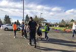 Eugene police officers and teachers escort students at Cascade Middle School to be reunited with their waiting parents outside St. Mark's Catholic Church in Eugene, Ore., Friday, Jan. 11, 2019. Eugene police Lt. Jennifer Bills told reporters that the incident began with a dispute outside the school. It wasn't clear who was involved and no further details were released. (AP Photo/Andrew Selsky)
