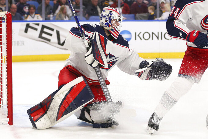 THIS CORRECTS THAT KIVLENIEKS DIED OF CHEST TRAUMA FROM AN ERRANT FIREWORKS MORTAR BLAST AND NOT A SUBSEQUENT FALL AS AUTHORITIES PREVIOUSLY REPORTED - FILE - Columbus Blue Jackets goalie Matiss Kivlenieks (80) makes a save during the first period of an NHL hockey game against the Buffalo Sabres in Buffalo, N.Y., in this Saturday, Feb. 1, 2020, file photo. The Columbus Blue Jackets and Latvian Hockey Federation said Monday, July 5, 2021, that 24-year-old goaltender Matiss Kivlenieks has died. A medical examiner in Michigan says an autopsy has determined that Columbus Blue Jackets goaltender Matiss Kivlenieks died of chest trauma from an errant fireworks mortar blast, and not a fall as authorities previously reported. Police in Novi, Michigan, said the mortar-style firework tilted slightly and started to fire toward people nearby Sunday night, July 4.  (AP Photo/Jeffrey T. Barnes, File)
