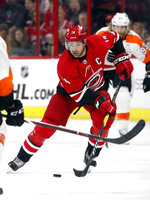 FILE - In this March 30, 2019, file photo, Carolina Hurricanes' Justin Williams (14) moves the puck against the Philadelphia Flyers during the third period of an NHL hockey game, in Raleigh, N.C. Justin Williams is back with the Carolina Hurricanes. The question now is how long it will take him to be ready for game action. The 38-year-old former captain said Wednesday he isn't sure exactly when he'll be ready to play, though he has been skating and working out in hopes of easing the transition back to the ice after he stepped away from the sport last fall. (AP Photo/Chris Seward, File)