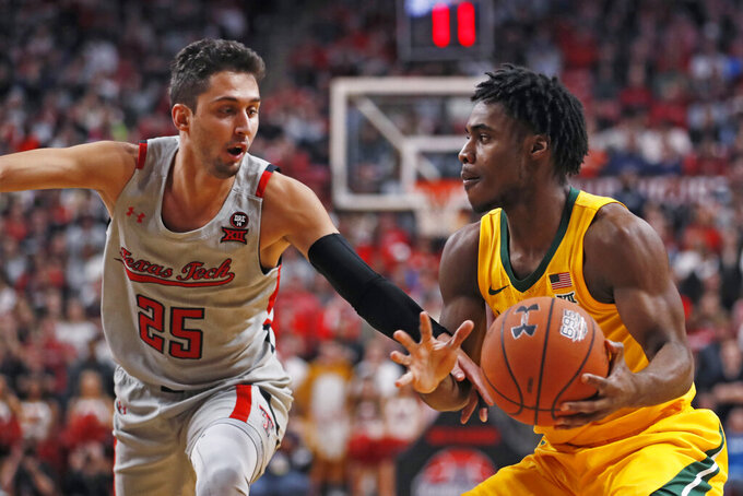 Texas Tech's Davide Moretti (25) tries to steal the ball from Baylor's Davion Mitchell during the first half of an NCAA college basketball game Tuesday, Jan. 7, 2020, in Lubbock, Texas. (AP Photo/Brad Tollefson)