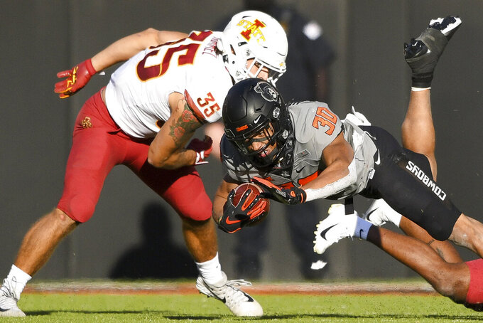 Iowa State linebacker Jake Hummel (35) watches as Oklahoma State running back Chuba Hubbard (30) leaps forward during an NCAA college football game Saturday, Oct. 24, 2020, in Stillwater, Okla.  (AP Photo/Brody Schmidt)