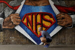 A jogger stops to tie his shoelace next to a recently painted NHS (National Health Service) Superman design mural by street artist Lionel Stanhope during the coronavirus lockdown, in the Waterloo area of London, Sunday, May 3, 2020. The highly contagious COVID-19 coronavirus has impacted on nations around the globe, many imposing self isolation and exercising social distancing when people move from their homes. (AP Photo/Matt Dunham)