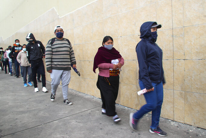 Voters wearing masks to curb the spread of the COVID-19 line up at a polling station during runoff presidential election in Quito, Ecuador, Sunday, April 11, 2021. Ecuadorians are voting to choose between Andres Arauz, from the Union of Hope coalition, an economist protégé of former President Rafael Correa, and former banker Guillermo Lasso, of Creating Opportunities party, or CREO. (AP Photo/Dolores Ochoa)