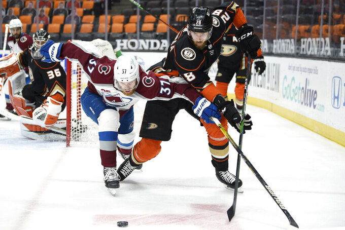 Colorado Avalanche left wing J.T. Compher, left, lunges for the puck against Anaheim Ducks defenseman Jani Hakanpaa during the first period of an NHL hockey game in Anaheim, Calif., Friday, April 9, 2021. (AP Photo/Kelvin Kuo)