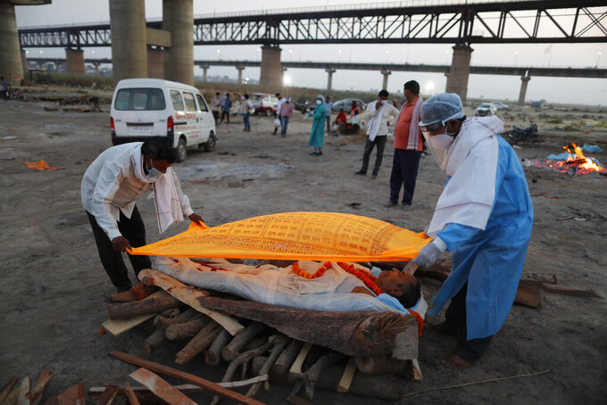 Family members place a cloth on the body of Rajendra Prasad Mishra, 62, who died due to COVID-19 before cremation by the River Ganges in Prayagraj, India, Saturday, May 8, 2021. (AP Photo/Rajesh Kumar Singh)