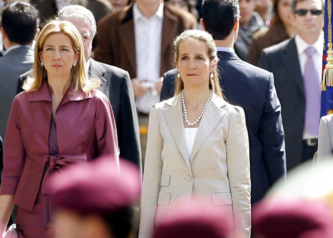 """FILE - In this Wednesdday, April 16, 2008 file photo, Spain's Princess Cristina, left and Princess Elena, listen to the Spanish national anthem during a ceremony, upon their arrival for the opening of the Spanish Parliament, after Jose Luis Rodriguez Zapatero's Socialist Party won the general elections on March 9, in Madrid. The sisters of Spanish King Felipe VI have acknowledged on Wednesday, March 3, 2021, that they were administered COVID-19 vaccines during a visit to the United Arab Emirates. In a statement published by a Spanish newspaper, the Infantas Elena and Cristina said that they were """"offered the possibility"""" of receiving vaccines while in Abu Dhabi to visit their father and former monarch, Juan Carlos I.  (AP Photo/Daniel Ochoa de Olza, File)"""