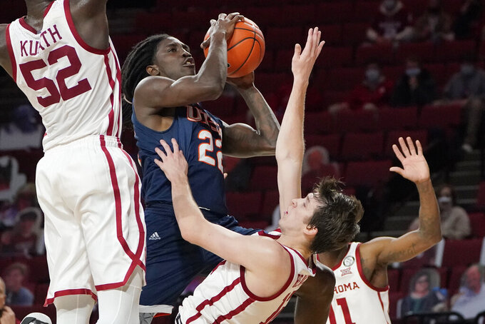 UTSA guard Keaton Wallace (22) commits an offensive foul on Oklahoma guard Austin Reaves, right, as he shoots during the first half of an NCAA college basketball game Thursday, Dec. 3, 2020, in Norman, Okla. (AP Photo/Sue Ogrocki)