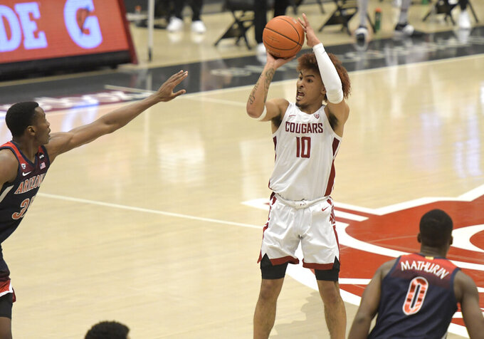 Washington State guard Isaac Bonton (10) hits a 3-point shot over Arizona center Christian Koloko , left, in the first half of an NCAA College Basketball game, Saturday, Jan. 2, 2021, in Pullman, Wash. (AP Photo/Dean Hare)