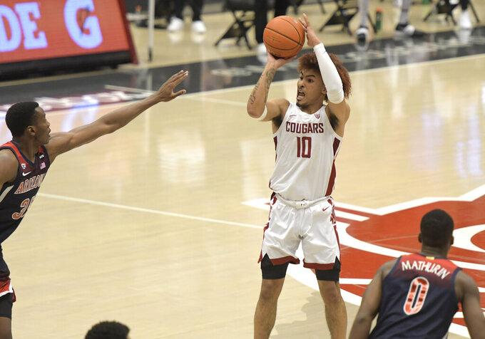 Washington State guard Isaac Bonton (10) hits a 3-point shot over Arizona center Christian Koloko , left, in the first half of an NCAA College Basketball game, Saturday, Jan. 2, 2021, in Pullman, Wash. (AP Photo/Dean Hare)