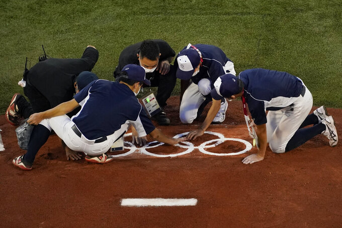 Workers place the Olympic rings on the pitching mound ahead of a baseball game between The Dominican Republic and South Korea at the 2020 Summer Olympics, Sunday, Aug. 1, 2021, in Yokohama, Japan. (AP Photo/Sue Ogrocki)