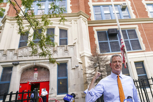FILE - In this Aug. 19, 2020, file photo, New York Mayor Bill de Blasio speaks to reporters after visiting New Bridges Elementary School to observe pandemic-related safety procedures, in the Brooklyn borough of New York. For most schoolchildren in New York City, Monday, Sept. 21, 2020, will mean back to school, but not back to the classroom. Only pre-kindergarteners and some special education students are scheduled to end a six-month absence from school buildings. (AP Photo/John Minchillo, FIle)