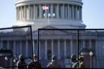With the U.S. Capitol in the background, members of the National Guard stand behind newly placed fencing around the Capitol grounds the day after violent protesters loyal to President Donald Trump stormed the U.S. Congress in Washington, Thursday, Jan. 7, 2021. (AP Photo/Evan Vucci)