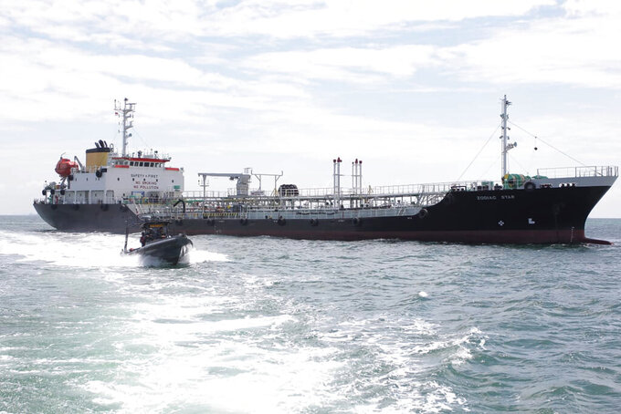 In this undated photo released by Indonesian Navy, a navy boat sails past Panamanian-flagged tanker MT Zodiac Star anchored in Riau Island waters, Indonesia. Indonesian navy seized the massive tanker believed to be loaded with thousands of tons of wasted black oil and has brought the ship to shore for further investigation, officials said Thursday, Sept. 2, 2021.(Indonesian Navy via AP)