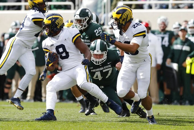 Michigan wide receiver Ronnie Bell (8) pulls away from Michigan State's Ryan Armour (47) during the first half of an NCAA college football game, Saturday, Oct. 20, 2018, in East Lansing, Mich. (AP Photo/Carlos Osorio)