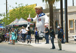 Protesters place a large inflatable balloon in the likeness of President Donald Trump dressed in a Ku Klux Klan sheet across the street from Southwest Key Campbell, a shelter for children that have been separated from their parents, in Phoenix, Ariz., Thursday, June 28, 2018, during a visit by first lady Melania Trump. (AP Photo/Carolyn Kaster)