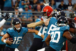 Jacksonville Jaguars quarterback Trevor Lawrence (16) tries to avoid a tackle by Cleveland Browns defenders during the first half of an NFL preseason football game, Saturday, Aug. 14, 2021, in Jacksonville, Fla. (AP Photo/Stephen B. Morton)