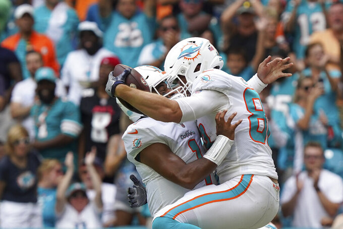 Miami Dolphins tight end Mike Gesicki (88), right, jumps to celebrate with Miami Dolphins quarterback Tua Tagovailoa (1), after scoring a touchdown during the second half of an NFL football game, Sunday, Oct. 24, 2021, in Miami Gardens, Fla. (AP Photo/Hans Deryk)