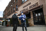 Employee Gina Hansen, right, hands documentation to a client outside Daniel J. Schaefer Funeral Home Thursday, April 2, 2020, in the Brooklyn borough of New York. The company is equipped to handle 40-60 cases at a time. But amid the coronavirus pandemic, it was taking care of 185 Thursday morning. (AP Photo/John Minchillo)