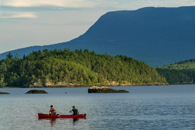 A man fishes from the bow of a canoe on Lobster Lake, Thursday, Aug. 13, 2020, in Lobster Township, Maine. Water levels in the lake are low this summer. The high water mark can be seen on the rock at center. (AP Photo/Robert F. Bukaty)
