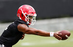 Georgia freshman quarterback Justin Fields (1) hands the ball to a running back during their NCAA college football training camp practice Friday, Aug. 3, 2018 in Athens, Ga. (AP Photo/John Bazemore)