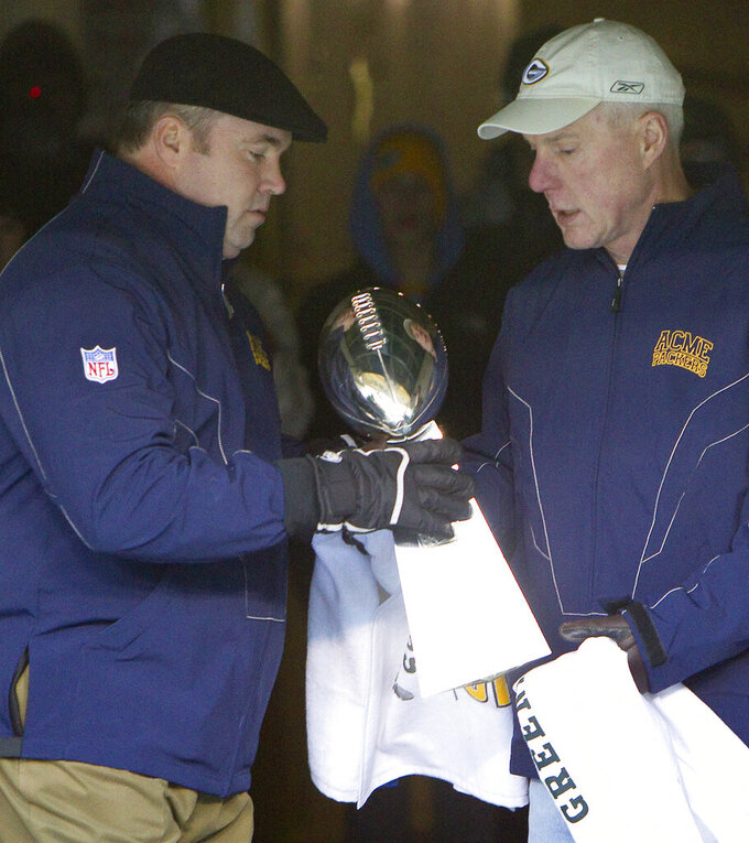 """FILE - In this Feb. 8, 2011, file photo, Green Bay Packers general manager Ted Thompson, right, hands the Vince Lombardi Trophy to coach Mike McCarthy before walking onto the field for the """"Return to Titletown"""" celebration at Lambeau Field in Green Bay, Wis. Thompson, whose 13-year run as Green Bay Packers general manager included their 2010 Super Bowl championship season, died Wednesday, Jan 20, the team announced Thursday, Jan. 21, 2021. He was 68. Thompson was Packers general manager from 2005-17 and drafted many notable players on the current roster, including two-time MVP quarterback Aaron Rodgers.  (AP Photo/Mike Roemer, File)"""
