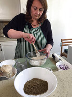 Tiziana di Costanzo, co-founder of Horizon Insects, stirs flour for pizza dough before adding cricket powder, pictured in foreground, in her London kitchen on June 2, 2021. While insects are commonly eaten in parts of Asia and Africa, they're increasingly seen as a viable food source in the West as Earth's growing population puts more pressure on global food production. Experts say they're rich in protein, yet can be raised much more sustainably than beef or pork. Regulatory change has also made things easier for European companies looking to market insects directly to consumers. (AP Photo/Kelvin Chan)