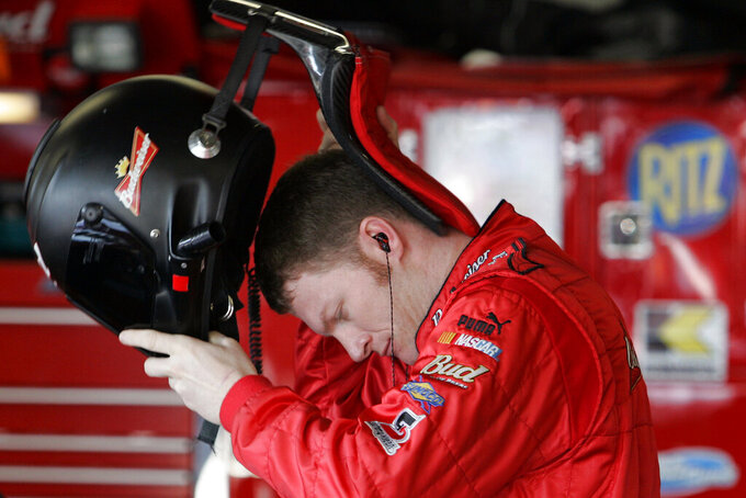 FILE - In this Feb. 18, 2006, file photo, Dale Earnhardt Jr., puts on his helmet and protective HANS device during preparations the day before the Daytona 500 auto race at Daytona International Speedway in Daytona Beach, Fla. NASCAR mandated the use of head-and-neck restraints in late 2001. Drivers had resisted using the U-shaped neck restraint made of carbon fiber because they found it cumbersome and restrictive. They became required equipment after 25-year-old Blaise Alexander was killed in a crash at Charlotte Motor Speedway some eight months after Earnhardt's death.(AP Photo/Chris O'Meara, File)