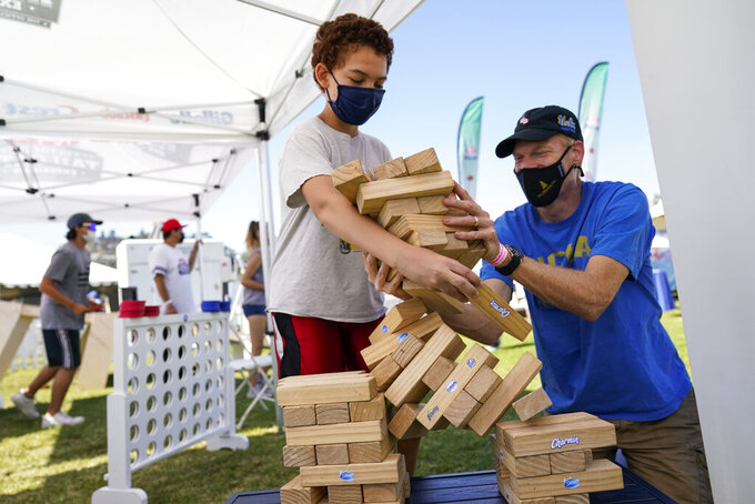 While wearing masks, David Bingener, 11, center, and Mark Bingener, right, play Jenga while tailgating before an NCAA college football game between the Hawaii Warriors and the UCLA Bruins, Saturday, Aug. 28, 2021, in Pasadena, Calif. California is seeing lower coronavirus transmission than other U.S. states as virus cases and hospitalizations decline following a summer surge. State health experts say relatively high vaccination rates ahead of the arrival of the delta variant made a difference. (AP Photo/Ashley Landis)