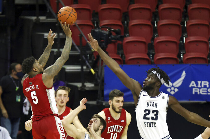 UNLV guard David Jenkins Jr. (5) shoots as Utah State center Neemias Queta (23) defends during the second half of an NCAA college basketball game in the quarterfinals of the Mountain West Conference men's tournament Thursday, March 11, 2021, in Las Vegas. (AP Photo/Isaac Brekken)