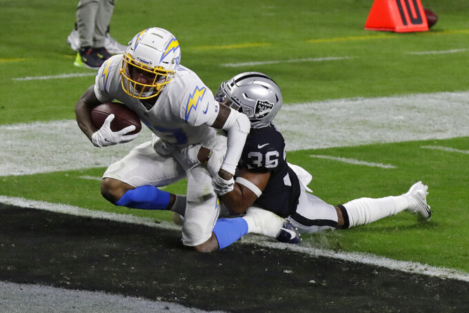 Los Angeles Chargers wide receiver Tyron Johnson (83) scores a touchdown against Las Vegas Raiders' Daryl Worley during the first half of an NFL football game, Thursday, Dec. 17, 2020, in Las Vegas. (AP Photo/Isaac Brekken)