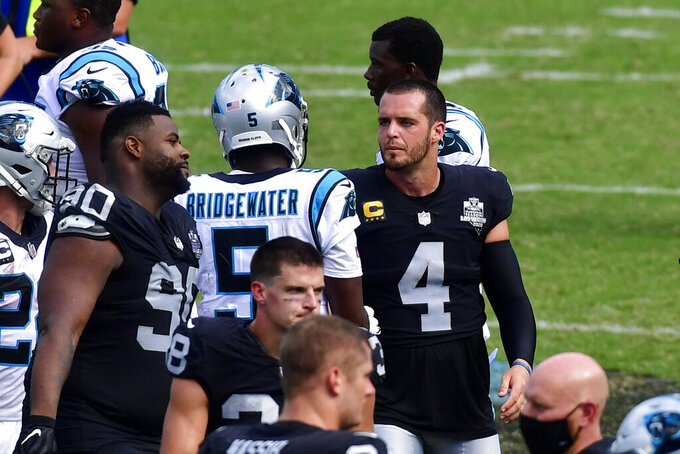 Las Vegas Raiders quarterback Derek Carr and Carolina Panthers quarterback Teddy Bridgewater meet on the field after an NFL football game Sunday, Sept. 13, 2020, in Charlotte, N.C. (AP Photo/Mike McCarn)