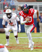 Mississippi quarterback Jordan Ta'amu (10) runs for a short gain while Auburn linebacker Big Kat Bryant (1) pursues during the first half of an NCAA college football game on Saturday, Oct. 20, 2018, in Oxford, Miss. (AP Photo/Rogelio V. Solis)