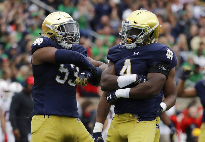 Notre Dame linebacker Te'Von Coney, right, celebrates with defensive line Khalid Kareem after he tackled Ball State quarterback Riley Neal during the first half of an NCAA college football game in South Bend, Ind., Saturday, Sept. 8, 2018. (AP Photo/Nam Y. Huh)