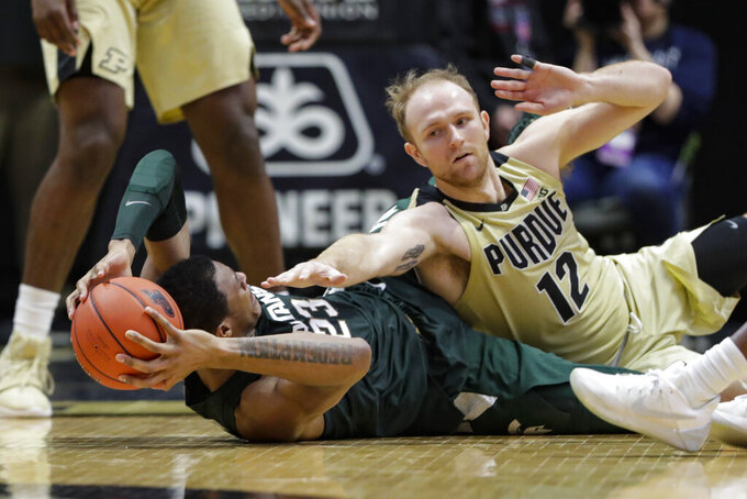 Purdue forward Evan Boudreaux (12) defends against Michigan State forward Xavier Tillman (23) on the floor during the second half of an NCAA college basketball game in West Lafayette, Ind., Sunday, Jan. 12, 2020. (AP Photo/Michael Conroy)
