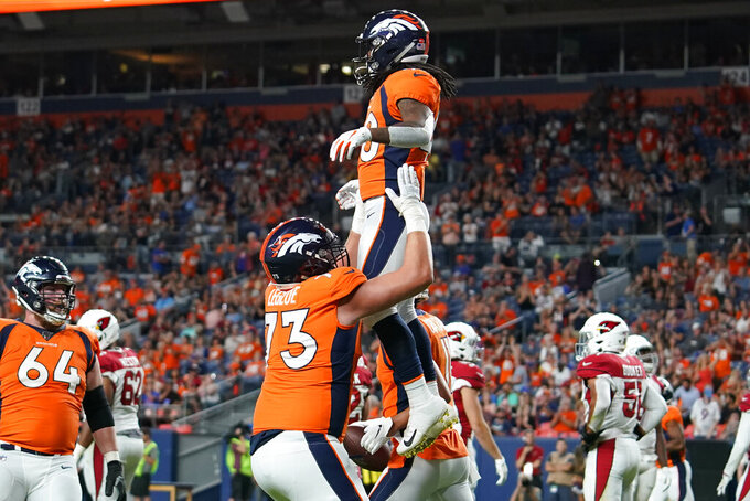 Denver Broncos offensive tackle John Leglue, left, lifts running back Devontae Jackson after Jackson scored a touchdown against the Arizona Cardinals during the second half of an NFL preseason football game, Thursday, Aug. 29, 2019, in Denver. (AP Photo/Jack Dempsey)
