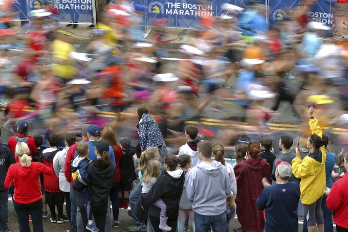 FILE - In this April 15, 2019, file photo, fans cheer on the third wave of runners at the start of the 123rd Boston Marathon in Hopkinton, Mass. Due to the COVID-19 virus pandemic, the 124th running of the Boston Marathon was postponed from its traditional third Monday in April to Monday, Sept. 14, 2020. (AP Photo/Stew Milne, File)