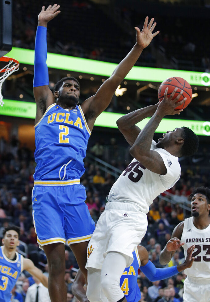 Arizona State's Zylan Cheatham attempts a shot around UCLA's Cody Riley during the second half of an NCAA college basketball game in the quarterfinals of the Pac-12 men's tournament Thursday, March 14, 2019, in Las Vegas. (AP Photo/John Locher)