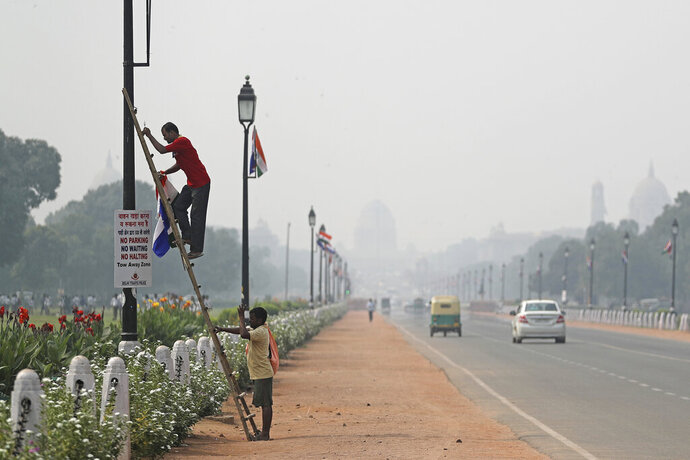 India's Presidential Palace, in the backdrop, is covered with smog as a municipal worker removes flags from a light pole along Rajapth, the ceremonial boulevard in New Delhi, India, Wednesday, Oct. 16, 2019. The Indian capital's air quality levels have plunged to