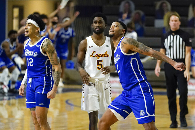 Drake forward Tremell Murphy, right, and guard Roman Penn, left, celebrate in front of Loyola of Chicago guard Keith Clemons (5) at the end of an NCAA college basketball game, Sunday, Feb. 14, 2021, in Des Moines, Iowa. Drake won 51-50 in overtime. (AP Photo/Charlie Neibergall)